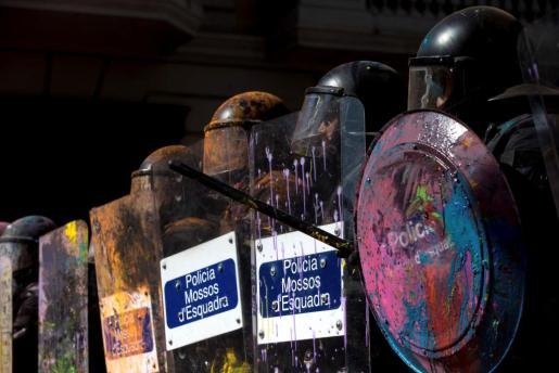 Agentes de los Mossos d'Esquadra cubiertos con pintura de colores que han lanzado los manifestantes independentistas que pretendían boicotear una manifestación de la asociación de policías y guardias civiles Jusapol, que ha rendido homenaje a los agentes de esos cuerpos que participaron el año pasado en el 1-O.