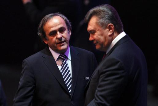 El presidente de la UEFA, Michel Platini, (i), charla con el presidente ucraniano Viktor Yanukovich (d) durante la celebración del sorteo de la fase final de la Eurocopa.