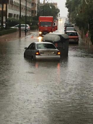 Imagen de una de las calles inundadas en la que un contenedor colisiona con un vehículo.