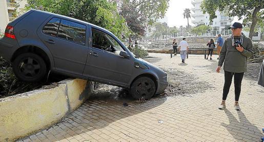 Un hombre contempla un coche afectado por la riada.