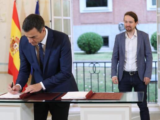 El presidente del Gobierno, Pedro Sánchez (i), y el secretario general de Podemos, Pablo Iglesias, durante la firma en el Palacio de la Moncloa del acuerdo sobre el proyecto de ley de presupuestos para 2019.