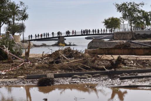 Continúa la búsqueda en S' Illot , del niño desaparecido tras las inundaciones de hace dos días en Sant Llorenç des Cardesar (Mallorca) . En la imágen , turistas observan los destrozos junto a la desembocadura del Torrente de Can Amer.