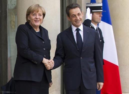 El presidente francés, Nicolas Sarkozy (dcha), da la bienvenida a la canciller alemana, Angela Merkel (izq), a su llegada al Palacio del Elíseo en París (Francia) hoy, lunes 5 de diciembre de 2011. Sarkozy se ha reunido con Merkel para avanzar, de cara a la cumbre europea de esta semana, las propuestas comunes para la reforma de la zona euro que han prometido, cuya elaboración sigue chocando con persistentes divergencias.