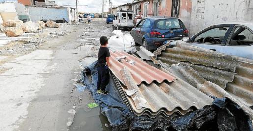 Un niño, sobre las uralitas que se han retirado de las viviendas derribadas del poblado de Son Banya.