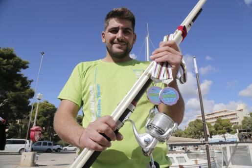 Josep Barceló posa con su caña y sus medallas en Portopetro.