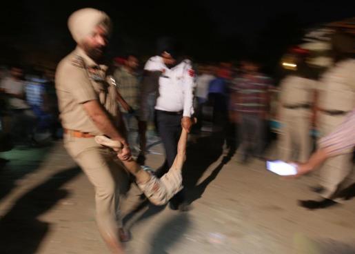 Agentes de policía transportan el cuerpo de una de las víctimas.