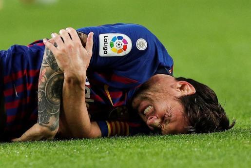 El delantero argentino del FC Barcelona, Leo Messi, se duele tras una jugada durante encuentro correspondiente a la novena jornada de primera división que disputan frente al Sevilla en el estadio del Camp Nou.