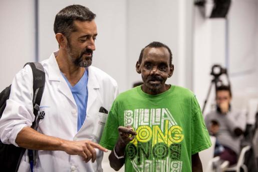 El cirujano español junto al paciente sometido a una reconstrucción parcial del rostro y la mano izquierda.