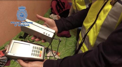 Un agente de la Policía Nacional sostiene uno de los aparatos que utilizaban para clonar tarjetas.