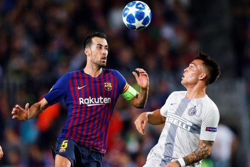 El centrocampista defensa del FC Barcelona Sergio Busquets (i) salta a por un balón con Lautaro Martínez, del Inter de Milán, durante el partido de la tercera jornada de la Liga de Campeones.