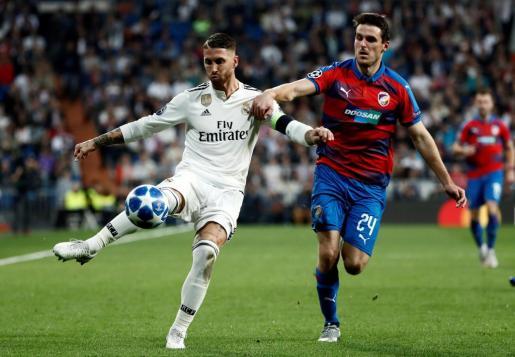El defensa del Real Madrid, Sergio Ramos (i), se dispone a golpear el balón ante el defensa del Viktoria Pilsen, Milan Havel, durante que ambos equipos disputaron en el Santiago Bernabéu.