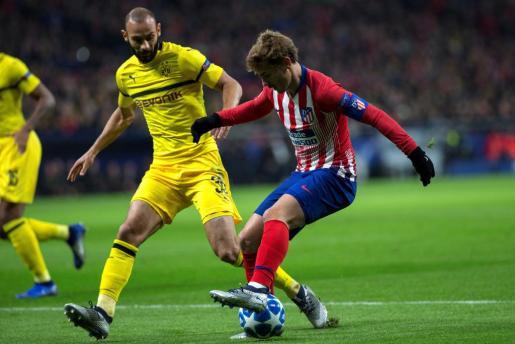 El delantero francés del Atletico de Madrid, Antoine Griezmann (d) pelea un balón con el defensa turco del Borussia Dortmund, Omer Toprak.