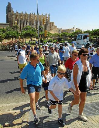 Turistas pasean por el Passeig Marítim un día de verano.