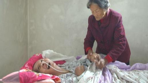 La madre cuidando a su hijo en coma.