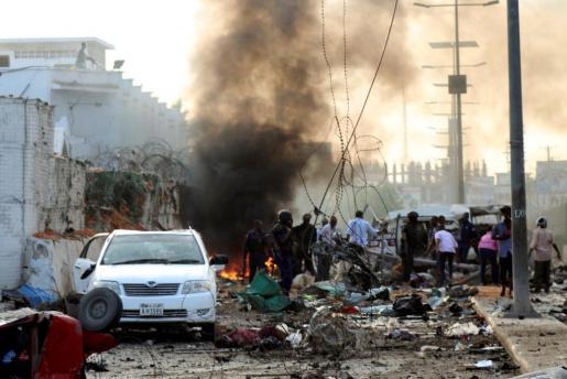 Policía y civiles ayudan en el lugar de un atentado bomba en un hotel de Mogadiscio (Somalia).
