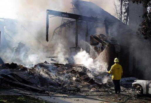 Un bombero extingue las llamas de un edificio en Agoura, California (Estados Unidos).