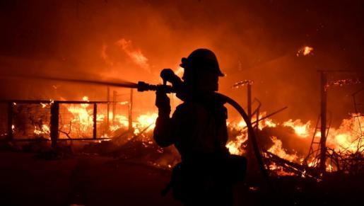Un bombero, luchando contra el fuego desatado en una vivienda de Malibú.