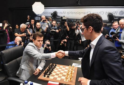 El noruego Magnus Carlsen, campeón mundial de ajedrez (i), saluda al aspirante al título, el estadounidense Fabiano Caruana (d), antes de comenzar la duodécima partida del Mundial de Ajedrez que se celebra en Londres (Reino Unido) hoy, 26 de noviembre del 2018. EFE/ Facundo Arrizabalaga Mundial de Ajedrez 2018