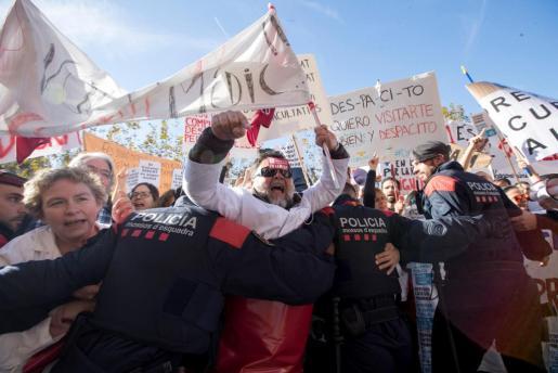 Mossos d'Esquadra tratan de impedir que los médicos de atención primaria que se concentran ante el Parlament, convocados por Médicos de Cataluña (MC), en la tercera jornada de huelga para exigir mejoras asistenciales y laborales en el sistema de salud, entren en la cámara catalana.