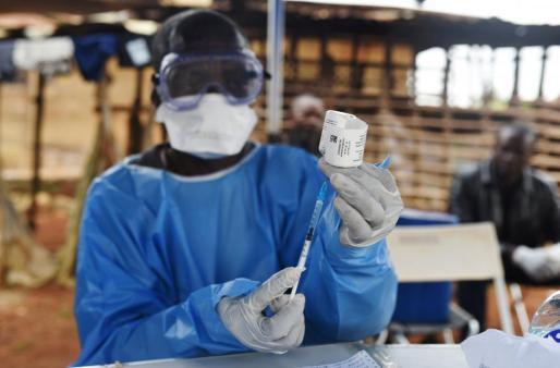 Un trabajador de salud congoleño se prepara para administrar la vacuna contra el ébola, en el exterior de la casa de una víctima de ébola en la aldea de Mangina, en la provincia de Kivu Norte.