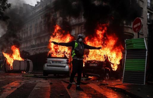 Un manifestante con un chaleco amarillo protesta por los precios del carburante junto a varios coches en llamas, en París.