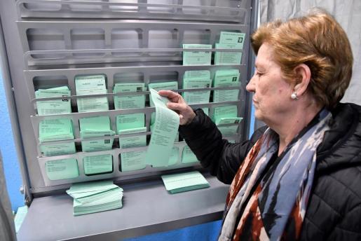 Una persona elige su papeleta electoral en un colegio del barrio San Luis de Almeria para ejercer su derecho a voto en las elecciones de Andalucía.