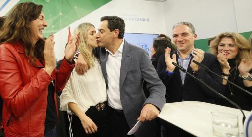 El candidato del Partido Popular a la presidencia de la Junta de Andalucía, Juan Manuel Moreno (c), besa a su esposa, Manuela Villena (2-i), en la comparecencia ante los medios tras conocer el resultado de las elecciones andaluzas.