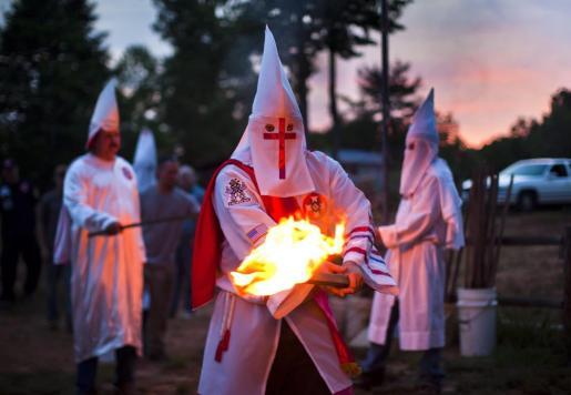 Un miembro de la orden de los Caballeros de la Brigada Rebelde del Ku Klux Klan (KKK) enciende una antorcha durante una ceremonia en una propiedad privada en Estados Unidos.