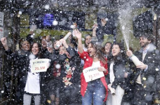 """Los propietarios de la Administración de lotería """" Doña Manolita"""" en la calle del Carmen en Madrid, celebran haber vendido el número 71.198 que ha sido agraciado con el Gordo de Navidad, en una imagen de archivo correspondiente al sorteo de la Lotería de Navidad de 2017."""