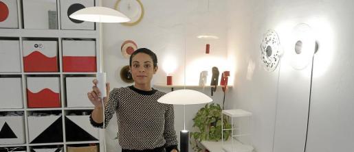 Tonia Fuster sostiene una de las lámparas fabricadas por ella misma junto a otros diseños que combinan los tonos blancos, negros y rojos y tienen un uso inteligente.