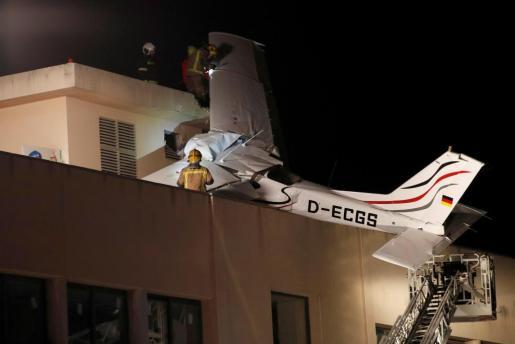 Los bomberos y servicios de emergencias en el tejado junto a la avioneta siniestrada.