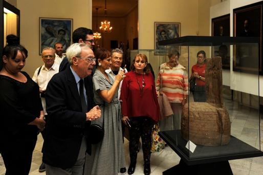 Noguera, entre otros, contempla la silla de Maceo, ya en el museo de La Habana.