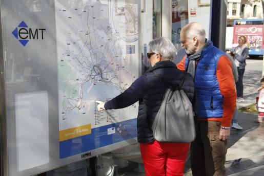 Una pareja de turistas consulta las rutas de la EMT.