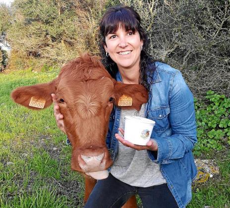 Cati Mingorance, promotora del proyecto Gelat Rural, junto a una de las vacas rojas menorquinas.