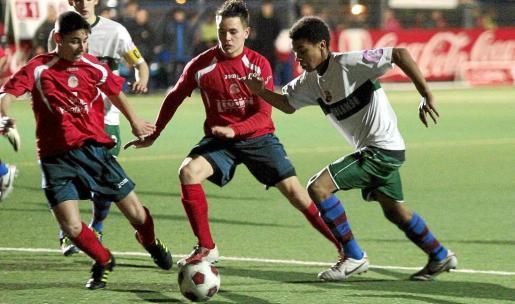 Un jugador del Poblense intenta abrirse paso ante la presión defensiva de dos futbolistas del Santa Catalina Atlético.