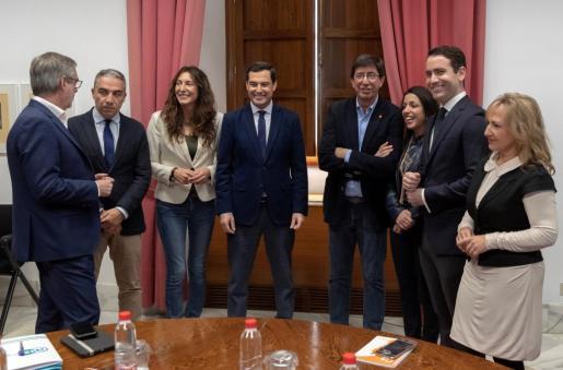 Los equipos negociadores del Partido Popular y Ciudadanos, encabezados por Juanma Moreno (4i), y Juan Marín (4d), al comienzo de la reunión que mantienen en Sevilla, un día antes de la constitución del Parlamento andaluz, para la configuración de la Mesa de la cámara regional.