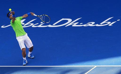 El tenista Rafael Nadal sirve ante Roger Federer en el torneo de exhibición de Abu Dhabi.