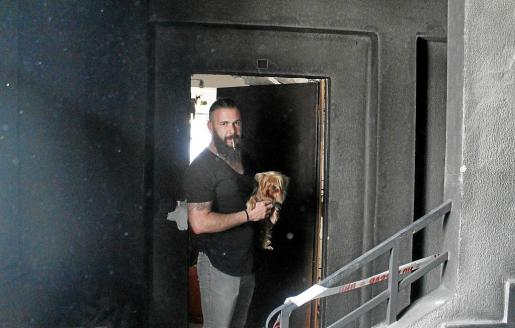 Javier Ros, junto a su perro, muestra el estado en el que han quedado los pisos afectados por el incendio de Camp Redó.