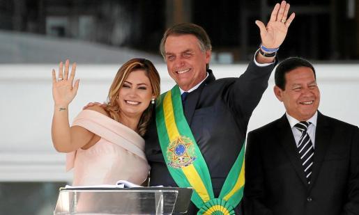 El nuevo presidente brasileño, con su esposa, Michelle Bolsonaro, saluda desde el Palacio de Planalto.