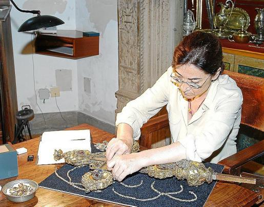 Elvira González descolgando las joyas.