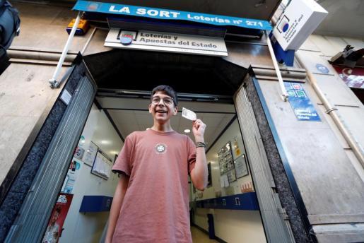 Cosmin, joven que adquirió el décimo agraciado con el primer premio de la loteria del Niño, muestra su décimo con el 37.142 , dotado con dos millones de euros por serie.