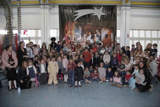 Los 58 niños, con algunos de sus papás y Carme Serra, presidenta del Grup Serra, con Sus Majestades los Reyes Magos de Oriente, y sus pajes.