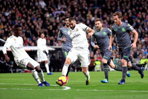 El delantero francés del Real Madrid Karim Benzema intenta escaparse de la defensa de la Real Sociedad.