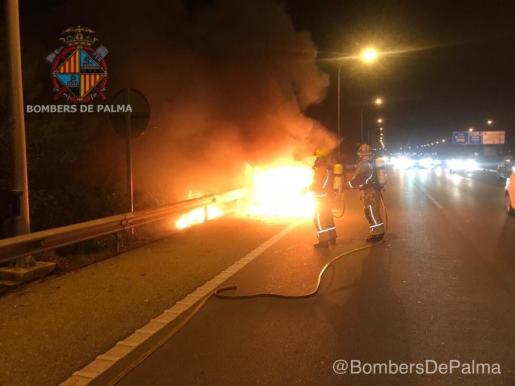 Los bomberos controlando el fuego que se ha generado en la parte delantera del coche.