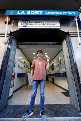 Cosmin, joven que adquirió el décimo agraciado con el primer premio de la loteria del Niño, muestra su décimo con el 37.142.