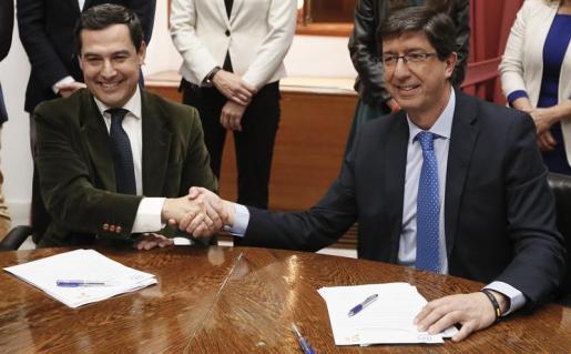 El presidente andaluz del Partido Popular, Juanma Moreno (i), y el de Ciudadanos, Juan Marín (d), estrechan las manos durante la reunión que han tenido esta tarde en el Parlamento de Andalucía para sellar su acuerdo de gobierno en la comunidad para la investidura del líder popular.