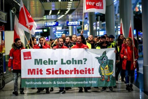 Manifestantes protestan este jueves en el aeropuerto de Düsseldorf (Alemania) durante la huelga parcial del personal de seguridad convocada por los sindicatos para reclamar mejoras salariales en la negociación del convenio colectivo.