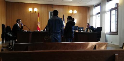 El cocinero acusado de abusar de una compañera, junto a la intérprete, durante el juicio.