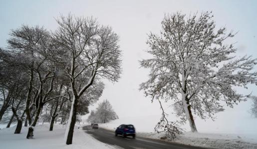 Coches circulan por una carretera cubierta de nieve en Reitham, Baviera.