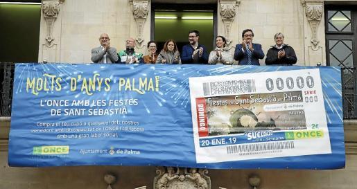 Representantes municipales y de la ONCE, ante una lona instalada en el balcón de Cort con la imagen del cupón de las fiestas.